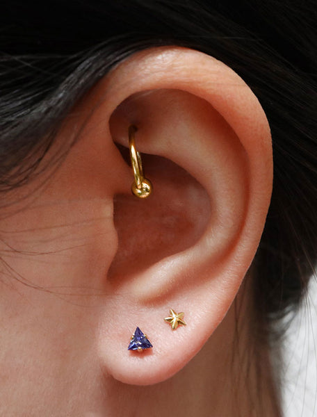 tiny sapphire triangle stud earrings modelled, september birth stone
