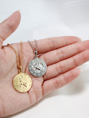 gold and silver large horoscope pendants in hand