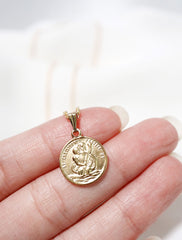 close up of tiny st christopher medal