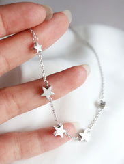 silver string of stars necklace in hand