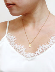 gold ribbon tag necklace modelled