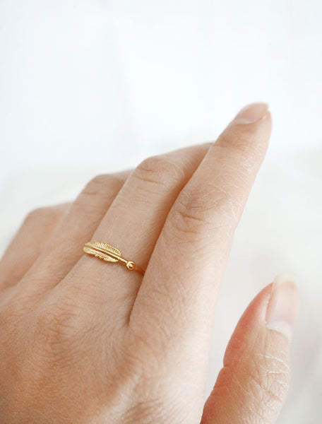 gold feather stacking ring worn