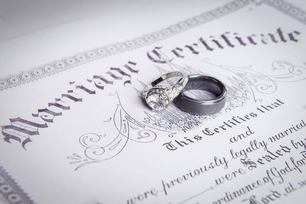 marriage license beneath wedding ring set