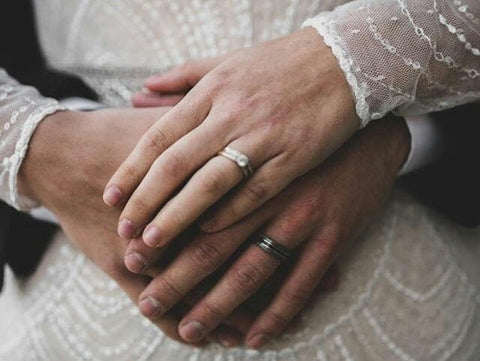 bride and groom holding hands showing off wedding rings