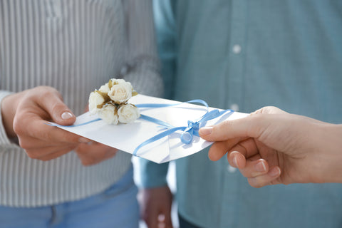 handing out paper wedding invitation