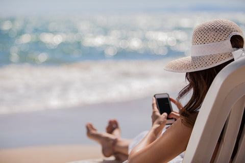 woman on her phone while sitting at the beach