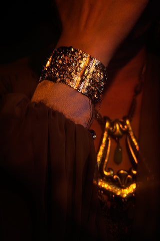 Close up of Icon Style gold bracelet and fringed necklace
