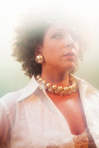 Sylvia Holden wears 70s pearl and lucite necklace and earrings in a wash of white light