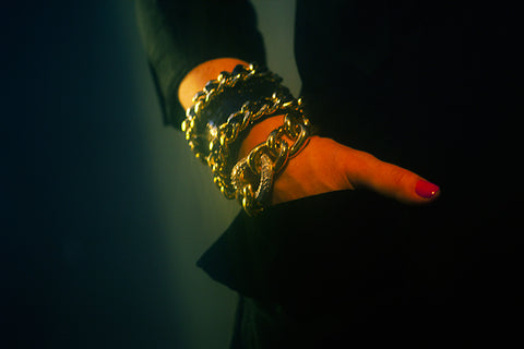 Hand in pocket with crocodile cuff bracelet with chain and Givenchy curb link bracelet