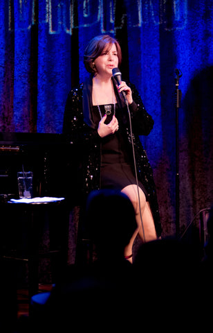 Celia Berk performing in a black dress and Icon Style jewelry