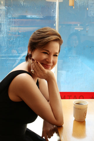 Celia Berk in a black dress and Icon Style jewelry in a coffee shop