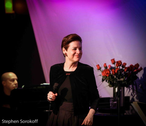 Celia Berk performs with a purple background and roses behind her, wearing red earrings from Icon Style