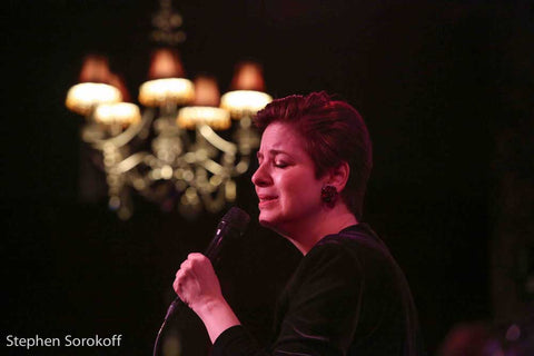 Celia Berk performs in red earrings from Icon Style with a chandelier in the background