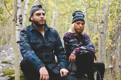 couple sitting in forest wearing grassroots gear