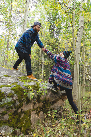 guy helping girl climb a rock in grassroots style