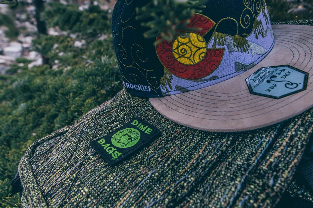 e08a7b4721660 Pictured  Dime Bags Urban Backpack in Timber and Grassroots Dabroots 2018  Navy Snapback.