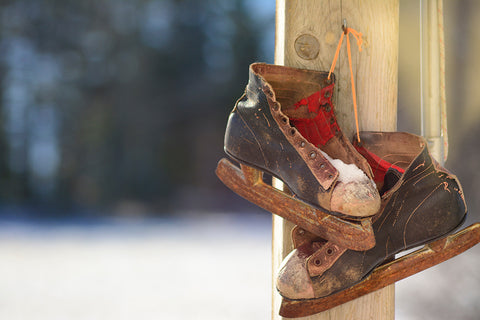 old black and white ice skates hanging on a post