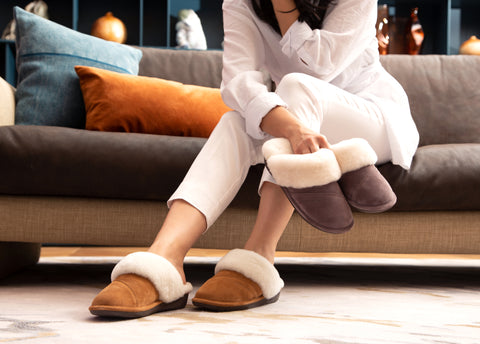 Woman wearing and holding slippers