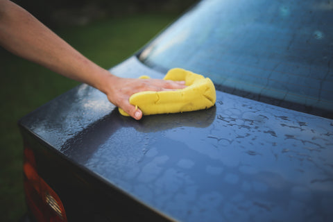 Man cleaning car with yellow cloth