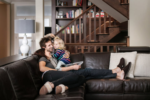 Mother, father and child wearing Nuknuuk slippers on the couch