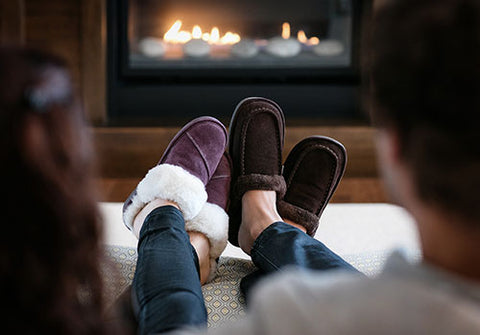 Couple sitting by fireplace wearing Nuknuuk slippers