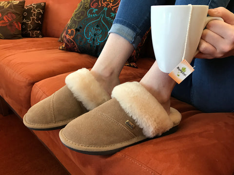 "Woman on couch with cup of tea wearing ""Becca women's slippers (Harvest)"" by Nuknuuk"