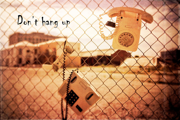 "Old dial up and push button telephones hanging on a wire fence with buildings in the background.  Textured photograph with quote ""Don't hang up""."