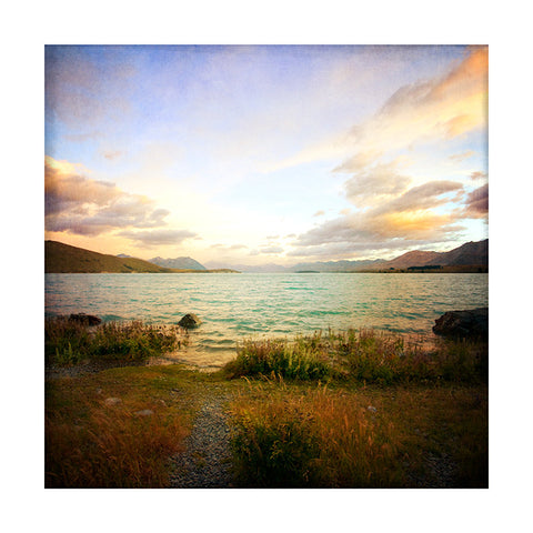 Photograph of Lake Tekapo in New Zealand. Lake, sun, sunset, clouds, water, rocks.
