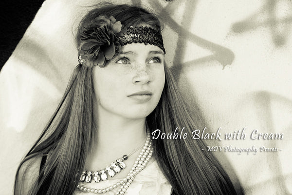 Black & white toned image of teen girl with long hair standing against a graffiti wall.