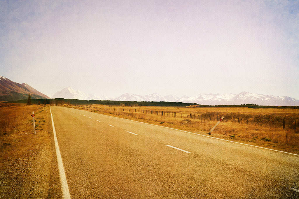 Photo of snowy mountains and a road on a sunny day with a Photoshop texture added.