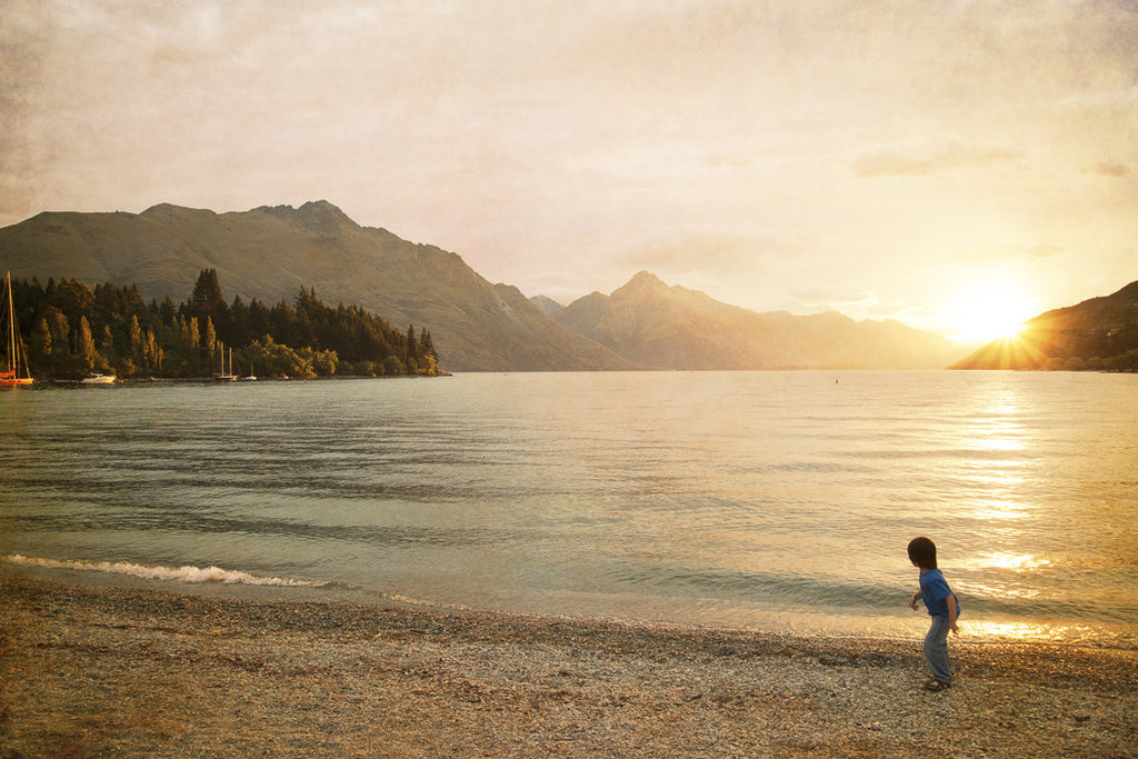 Photo of a little boy throwing a rock into Lake Wakatipu as the sun sets. Mountains in the distance.