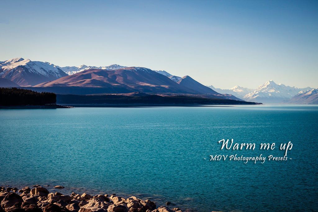 After lightroom preset 'Warm me up' applied - aqua blue lake with snow capped mountains in the distance