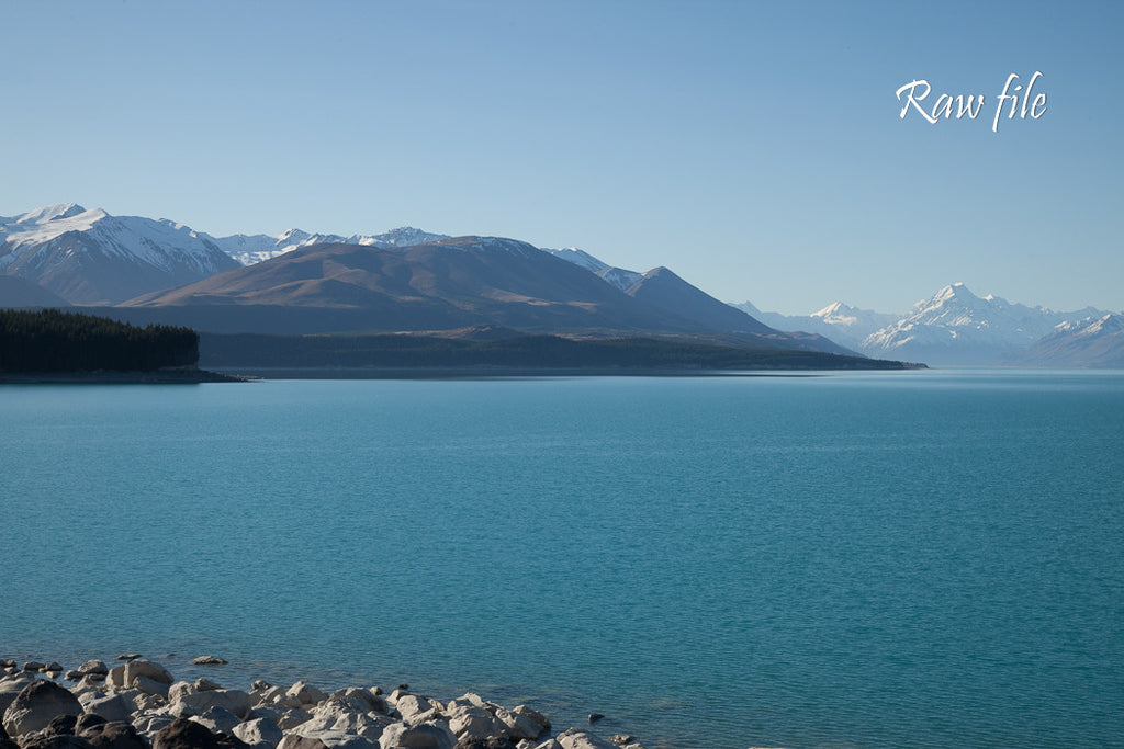Before lightroom preset applied - aqua blue lake with snow capped mountains in the distance
