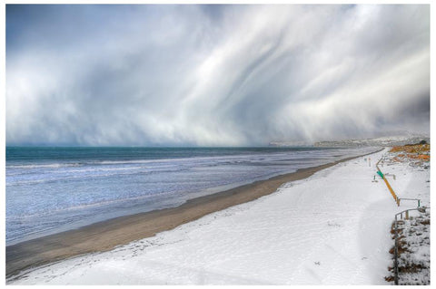 Snow on the beach at New Brighton, Christchurch.  Grey swirling storm clouds.
