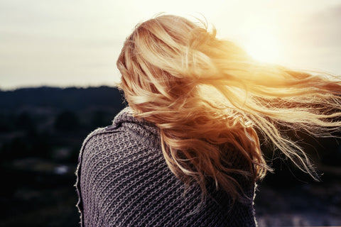 Young blonde woman facing sunset