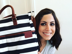 Jackie Oliva of As The Stroller Turns holds up her Hip Cub Medium Tote Diaper Bag