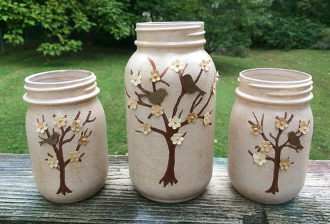 Set of 3 Hand Painted and Embellished Tree Mason Jars. Birds and Flowers adorn the hand painted trees on these shimmering pale beige jars