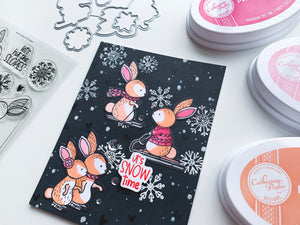 Skiing Bunnies with snow on a black card