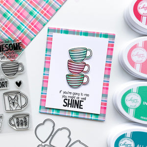 Three stacked striped mugs with plaid background