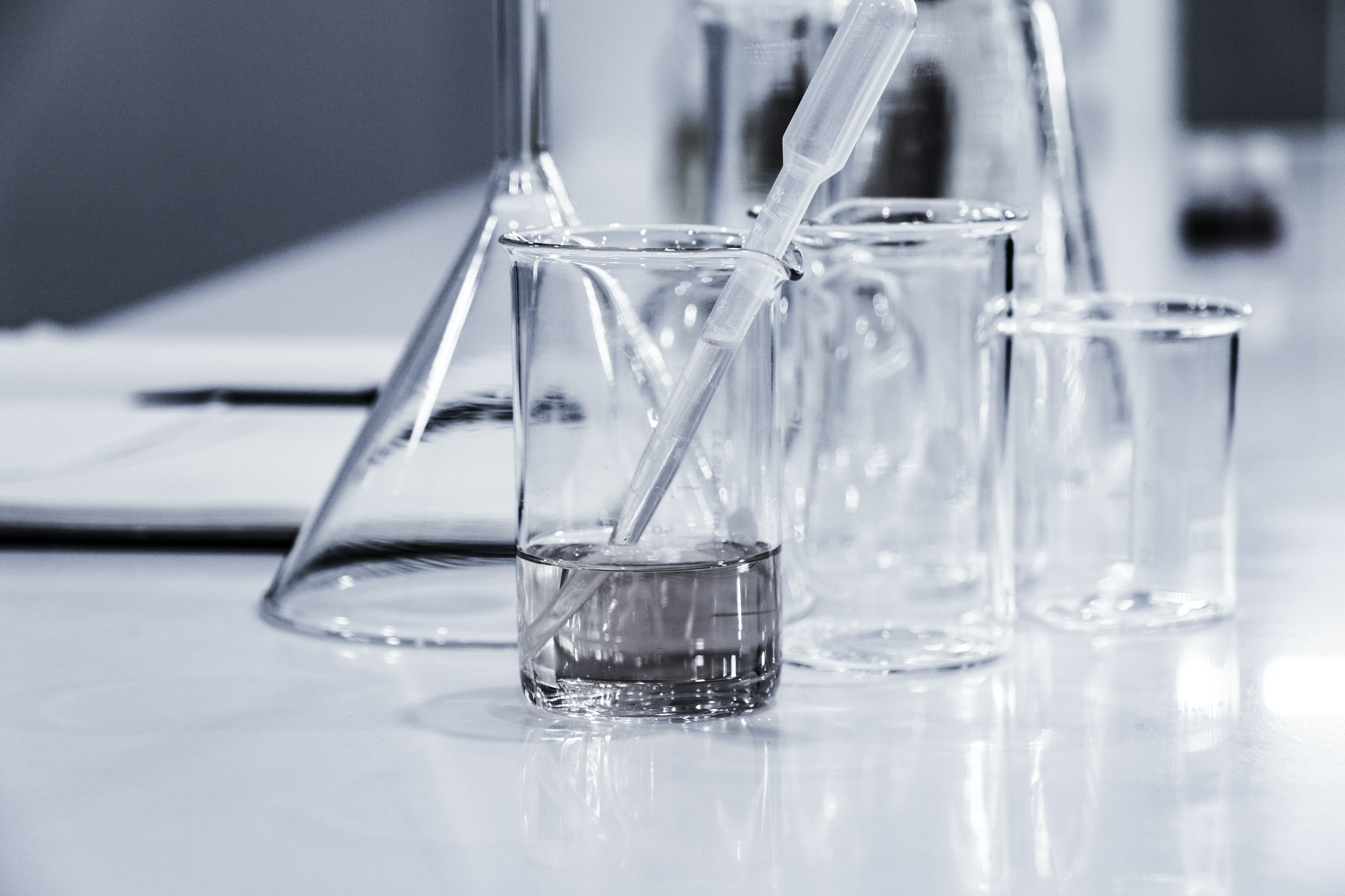 Photograph of a plastic pipette in a glass beaker filled with water, with empty glass beakers and a glass funnel in the background