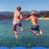 girl and boy jumping from rocks into crystal clear sea