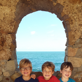 3 boys smiling in front of rock formation overlooking the Aegean Sea