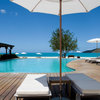 Sun loungers on pool deck overlooking turquoise infinity pool in Antigua