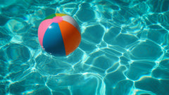 Close up of swimming pool water with reflective light and beach ball floating