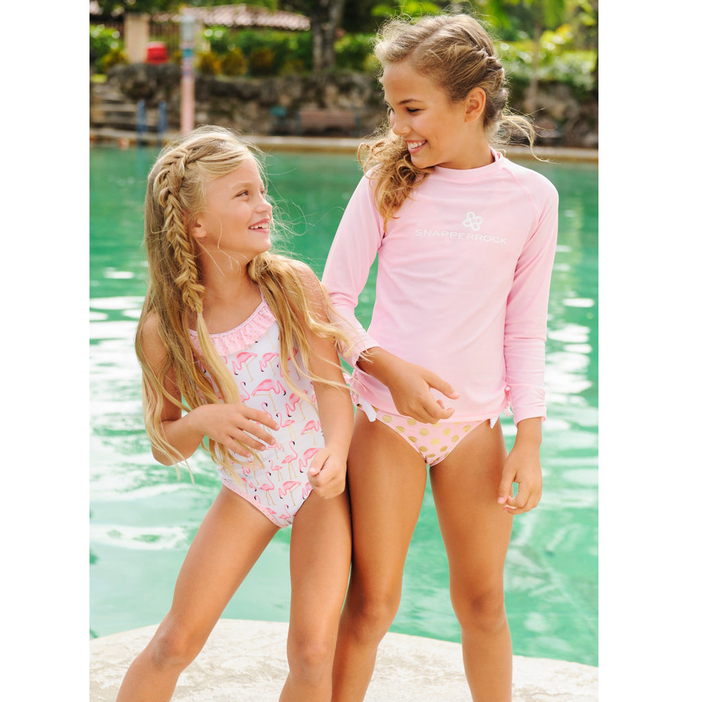 2 girls by pool, 1 wearing pink/gold ballet dots swimsuit with long sleeve pink rash vest over and 1 wearing pink flamingo swimsuit