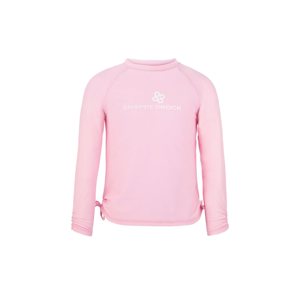 Pastel pink long sleeve rash vest with pretty tie side detail and white 'Snapper Rock' logo design across front. UV50+ protection