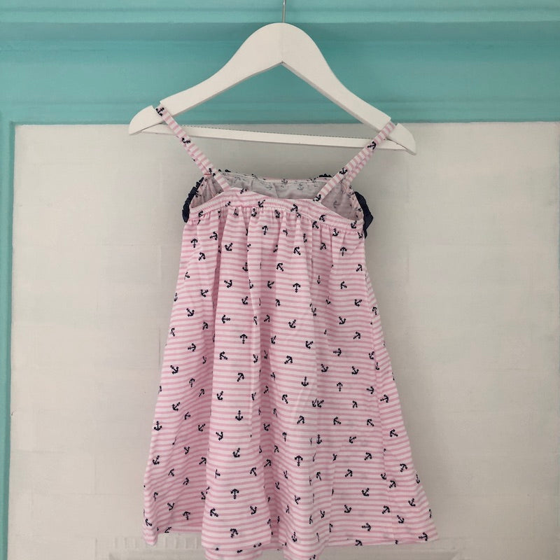 Back view of Pink and white stripe dress with navy anchor print, navy ruffle trim with bow at neckline and shoestring straps