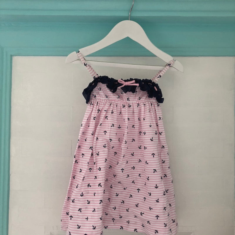 Front view of Pink and white stripe dress with navy anchor print, navy ruffle trim with bow at neckline and shoestring straps