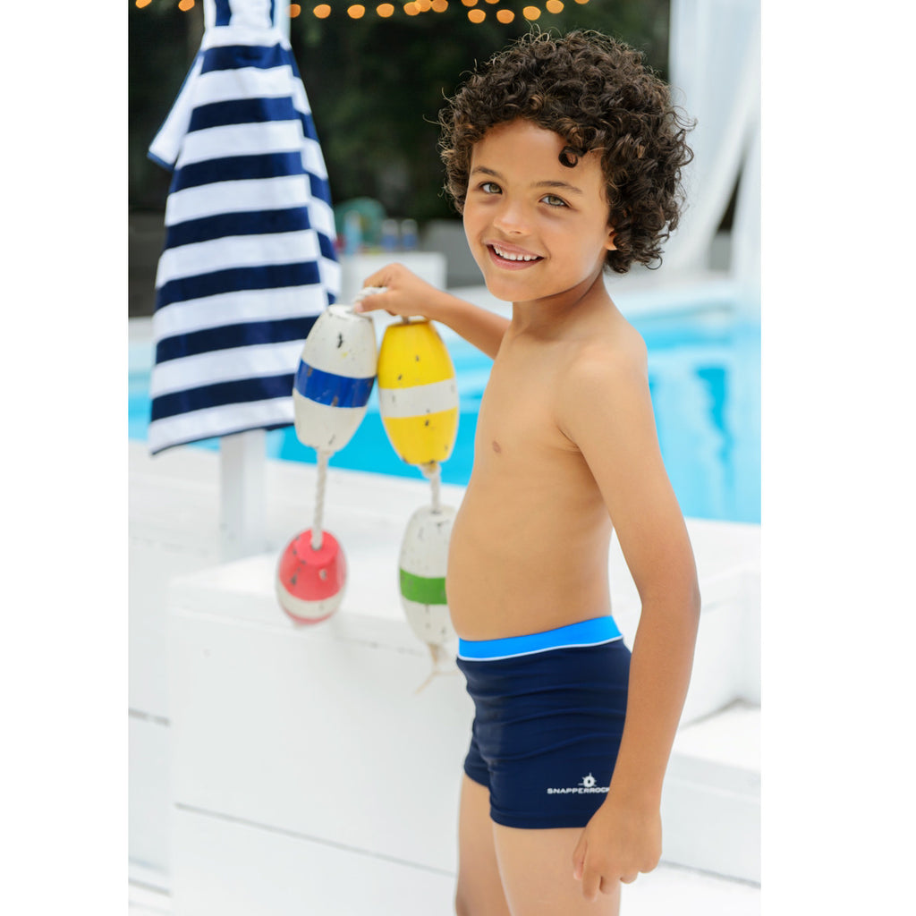 Boy by pool wearing navy fitted swim shorts with contrast midnight blue waistband and snapper rock logo to left leg