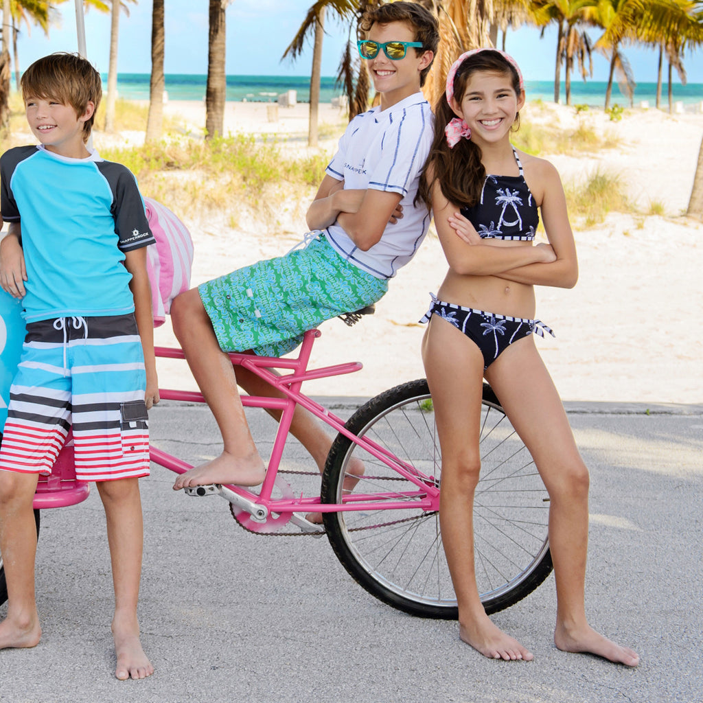 2 boys and girl on beach. Boy wearing classic surfer style long swim shorts in blue, red, charcoal and white stripe